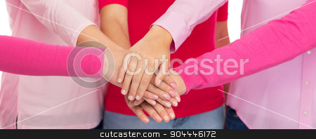 close up of women in pink shirts with hands on top stock photo, healthcare, people, gesture, breast cancer awareness and medicine concept - close up of women in pink shirts putting hands on top over white background by Syda Productions