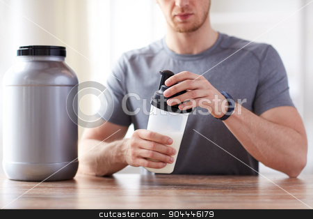 close up of man with protein shake bottle and jar stock photo, sport, fitness, healthy lifestyle and people concept - close up of man in fitness bracelet with jar and bottle preparing protein shake by Syda Productions