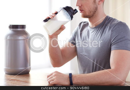 close up of man drinking protein shake stock photo, sport, fitness, healthy lifestyle and people concept - close up of man in fitness bracelet with jar and bottle drinking protein shake by Syda Productions