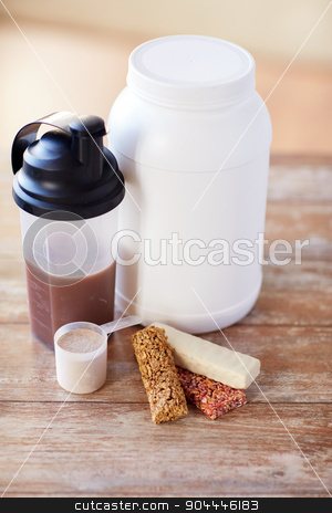 close up of protein food and additives on table stock photo, sport, fitness, diet and food concept - close up of jar, protein shake bottle and muesli bars on wooden table by Syda Productions