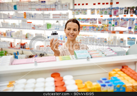 happy female customer with drug jar at pharmacy stock photo, medicine, pharmaceutics, health care and people concept - happy female customer with drug jar at pharmacy by Syda Productions
