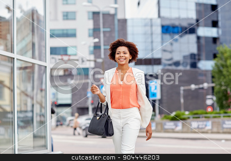 happy young african american businesswoman in city stock photo, business and people concept - young smiling african american businesswoman in city by Syda Productions