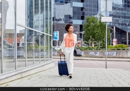 young african woman with travel bag in city stock photo, travel, business trip, people and tourism concept - young african american  woman with travel bag walking down city street by Syda Productions