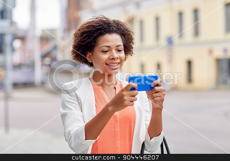 happy african businesswoman with smartphone stock photo, business, technology, communication and people concept - young smiling african american businesswoman with smartphone reading message on city street by Syda Productions
