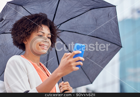 businesswoman with umbrella texting on smartphone stock photo, business, bad weather and people and concept - happy african american businesswoman with umbrella texting on smartphone at city street by Syda Productions