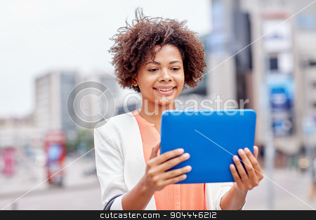 happy african businesswoman with tablet pc in city stock photo, business, technology, communication and people concept - young smiling african american businesswoman with tablet pc computer in city by Syda Productions