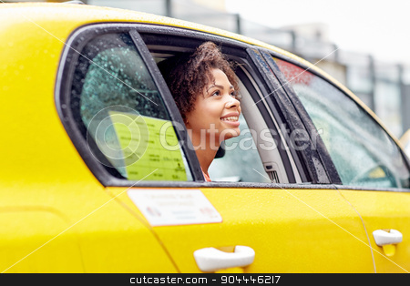 happy african american woman driving in taxi stock photo, business trip, transportation and people concept - young smiling african american woman driving in taxi at city street by Syda Productions