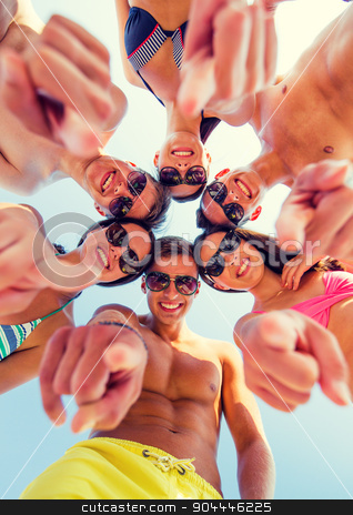 smiling friends in circle on summer beach stock photo, friendship, summer vacation, gesture and people concept - group of smiling friends wearing swimwear and pointing finger on you standing in circle over blue sky by Syda Productions