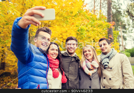 smiling friends with smartphone in city park stock photo, season, people, technology and friendship concept - group of smiling friends with smartphone taking selfie in autumn park by Syda Productions