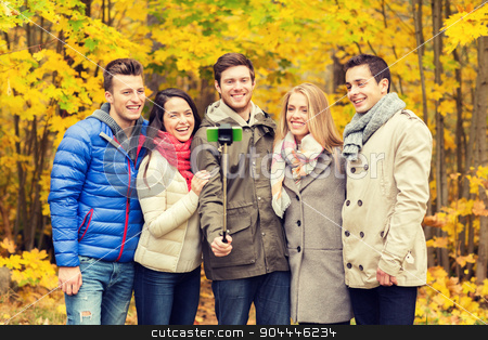 smiling friends with smartphone in city park stock photo, season, people, technology and friendship concept - group of smiling friends with smartphone and selfie stick taking picture in autumn park by Syda Productions