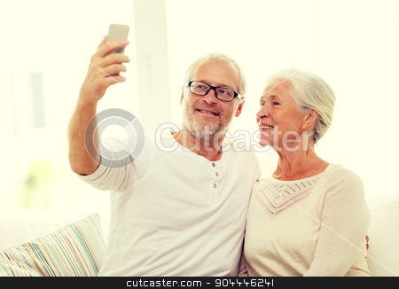 happy senior couple with smartphone at home stock photo, family, technology, age and people concept - happy senior couple with smartphone making selfie at home by Syda Productions