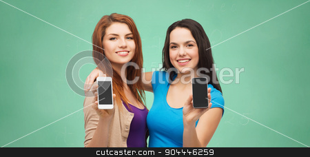 happy student girls showing smartphones screens stock photo, school, education, advertisement, people and modern technology concept - two smiling student girls or young women showing blank smartphones screens over blue sky with clouds background by Syda Productions