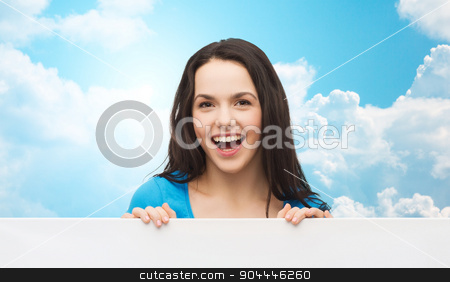 smiling young girl with blank white board stock photo, advertisement, sale and people concept - smiling young girl with blank white board over blue sky with clouds background by Syda Productions