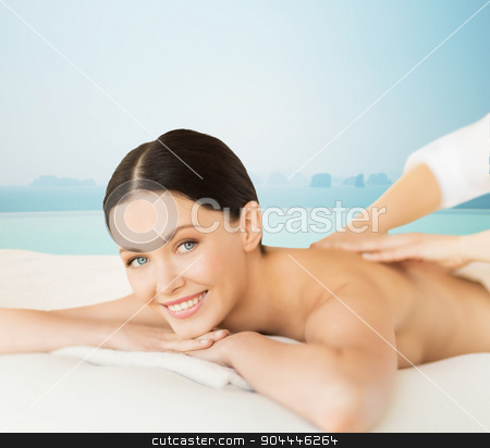happy beautiful woman having back massage stock photo, people, beauty, spa and body care concept - happy beautiful woman having back massage over sea and infinity pool background by Syda Productions