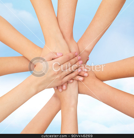 close up of hands on top stock photo, healthcare, people, gesture and medicine concept - close up of women hands on top of each other over blue sky background by Syda Productions