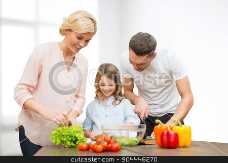 happy family cooking vegetable salad for dinner stock photo, vegetarian food, culinary, happiness and people concept - happy family cooking vegetable salad for dinner over white room background by Syda Productions