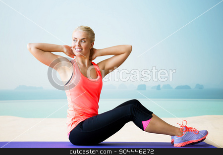 smiling woman doing sit-up on mat over pool stock photo, fitness, sport, exercising and people concept - smiling woman doing sit-up on mat over sea and pool at hotel resort background by Syda Productions