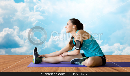 smiling woman stretching leg on mat over clouds stock photo, fitness, sport, training, technology and people concept - smiling woman with smartphone and earphones listening to music and stretching leg over wooden floor and sky with white clouds background by Syda Productions