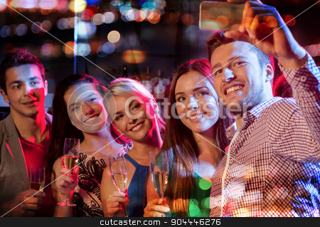 friends taking selfie by smartphone in night club stock photo, party, holidays, technology, nightlife and people concept - smiling friends with glasses of champagne and smartphone taking selfie in night club with holidays lights by Syda Productions