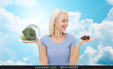 smiling woman with broccoli and donut over sky stock photo, healthy eating, junk food, diet and choice people concept - smiling woman choosing between broccoli and donut over blue sky and clouds background by Syda Productions