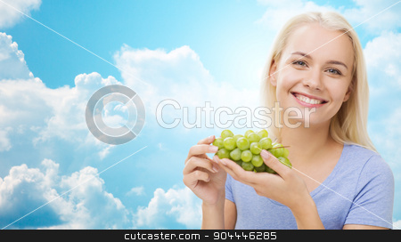 happy woman eating grapes over sky stock photo, healthy eating, food, fruits, diet and people concept - happy woman eating grapes over blue sky and clouds background by Syda Productions