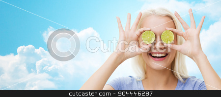 happy woman having fun covering eyes with lime stock photo, healthy eating, organic food, fruit diet, comic and people concept - happy woman having fun and covering her eyes with lime slices over blue sky and clouds background by Syda Productions