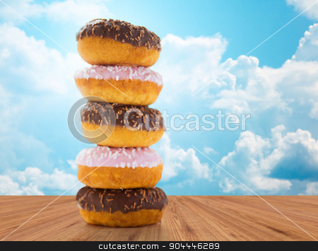 close up of glazed donuts pile over blue sky stock photo, food, junk-food and eating concept - close up of glazed donuts pile on wooden table over blue sky and clouds background by Syda Productions