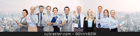 group of happy businesspeople with dollar money stock photo, business, people, finances and banking concept - group of happy businesspeople with money bags over city background by Syda Productions