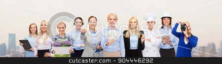 woman holding money over professional workers stock photo, people, profession, employment, compensation and finances concept - happy businesswoman holding dollar money with group of professional workers over city background by Syda Productions