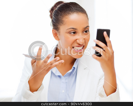 african woman shouting into smartphone stock photo, business, and communication concept - african woman shouting into smartphone by Syda Productions