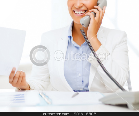 african businesswoman with phone in office stock photo, business, and communication concept - smiling african businesswoman with phone in office by Syda Productions
