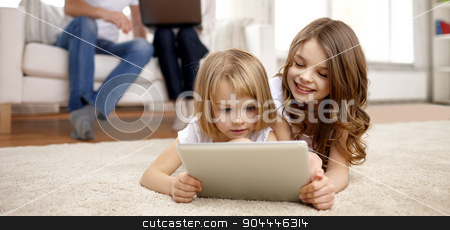happy little girls with tablet pc computer at home stock photo, people, family, technology and children concept - happy little girls playing with tablet pc computer at home by Syda Productions