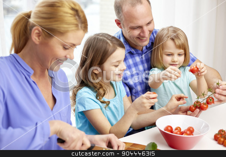 happy family with two kids cooking at home stock photo, food, children, culinary and people concept - happy family with two kids cooking vegetables at home by Syda Productions