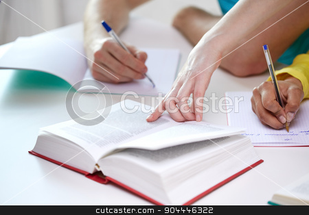 close up of students hands writing to notebooks stock photo, education, people and school concept - close up of students hands with textbooks writing to notebooks at school by Syda Productions