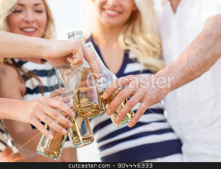close up of friends clinking bottles with drinks stock photo, vacation, celebration, holidays and people concept - close up of happy friends clinking bottles with drinks at party by Syda Productions