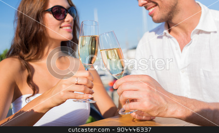 smiling couple clinking champagne glasses at cafe stock photo, love, dating, people and holidays concept - smiling couple wearing sunglasses drinking champagne and looking to each other at cafe by Syda Productions