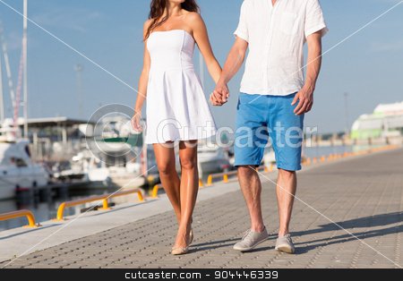 close up of couple holding hands and walking stock photo, love, travel, tourism, summer and people concept - close up of couple holding hands and walking along waterfront by Syda Productions