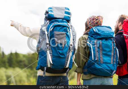 group of friends with backpacks hiking stock photo, adventure, travel, tourism, hike and people concept - group of friends walking with backpacks from back by Syda Productions
