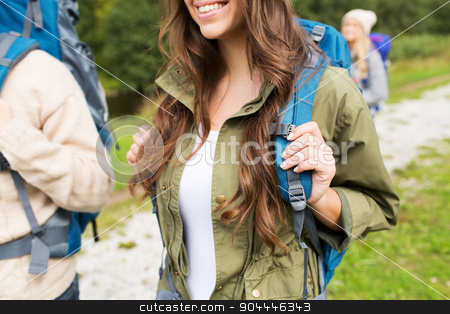 close up of woman with backpack hiking stock photo, adventure, travel, tourism, hike and people concept - close up of happy woman and her friends hikers with backpacks walking on hiking trail by Syda Productions