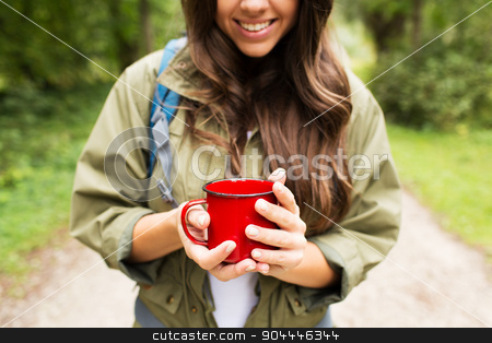 smiling young woman with cup and backpack hiking stock photo, adventure, travel, tourism, hike and people concept - smiling young woman hiker with cup and backpack in forest by Syda Productions