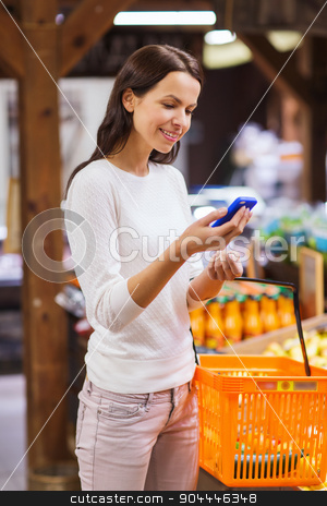 happy woman with basket and smartphone in market stock photo, sale, shopping, consumerism and people concept - happy young woman with food basket and smartphone in market by Syda Productions