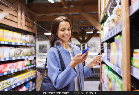 happy young woman with smartphone in market stock photo, sale, shopping, consumerism and people concept - happy young woman with smartphone choosing and buying food in market by Syda Productions