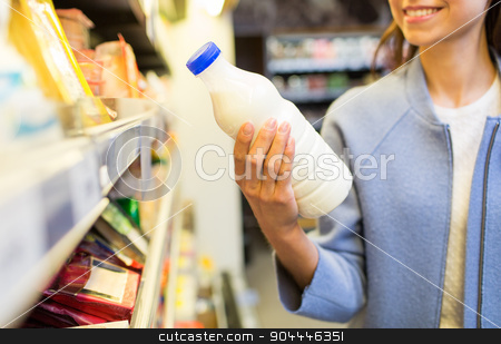 happy woman holding milk bottle in market stock photo, sale, shopping, consumerism, food and people concept - close up of happy young woman holding milk bottle in market by Syda Productions