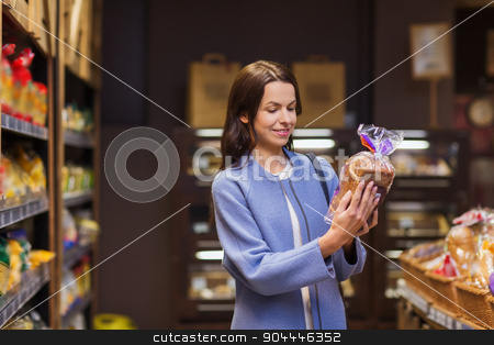 happy woman choosing and buying food in market stock photo, sale, shopping, consumerism and people concept - happy young woman choosing and reading label on bread in market by Syda Productions