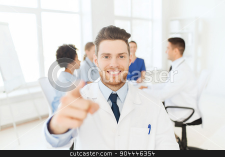 happy doctor over group of medics at hospital stock photo, clinic, profession, gesture, people and medicine concept - happy male doctor pointing finger at you over group of medics meeting at hospital by Syda Productions