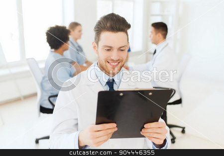 happy doctor with tablet pc over team at clinic stock photo, clinic, profession, people and medicine concept - happy male doctor with tablet pc computer over group of medics meeting at hospital by Syda Productions