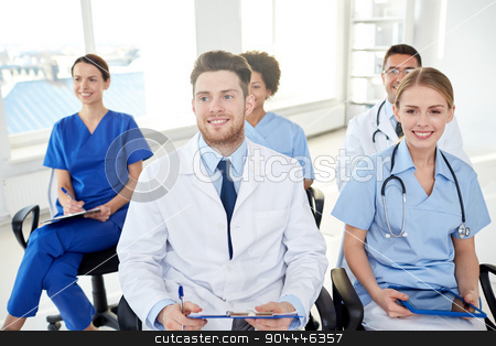 group of happy doctors on seminar at hospital stock photo, profession, medical education, health care, people and medicine concept - group of happy doctors on seminar in lecture hall at hospital by Syda Productions