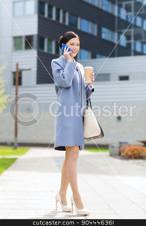 happy businesswoman calling on smartphone in city  stock photo, business and people concept - young smiling businesswoman calling on smartphone over office building by Syda Productions