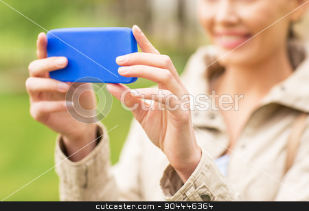 close up of woman taking picture with smartphone stock photo, drinks, leisure, technology and people concept - smiling woman taking picture or selfie with smartphone in park by Syda Productions
