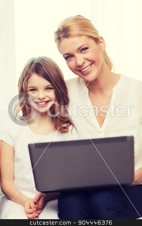 smiling mother and little girl with laptop at home stock photo, family, child, technology and home concept - smiling mother and little girl with laptop at home by Syda Productions